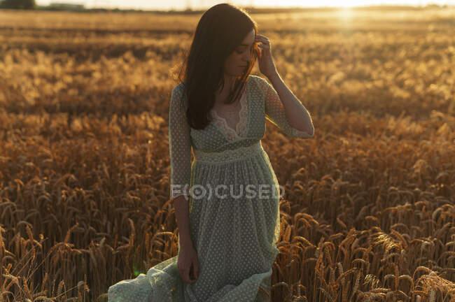 Молода жінка в одязі стоїть на фермі під час заходу сонця. — стокове фото