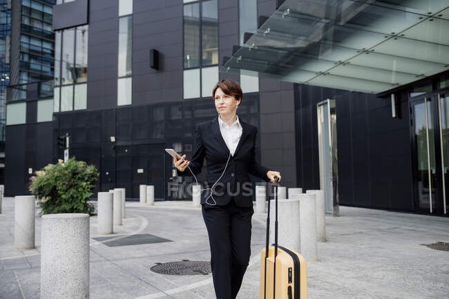 Female professional listening music while walking with suitcase against modern building — Fotografia de Stock