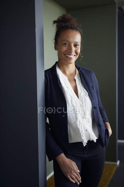 Портрет усміхненої ділової жінки, яка спирається на дверний чемодан — стокове фото