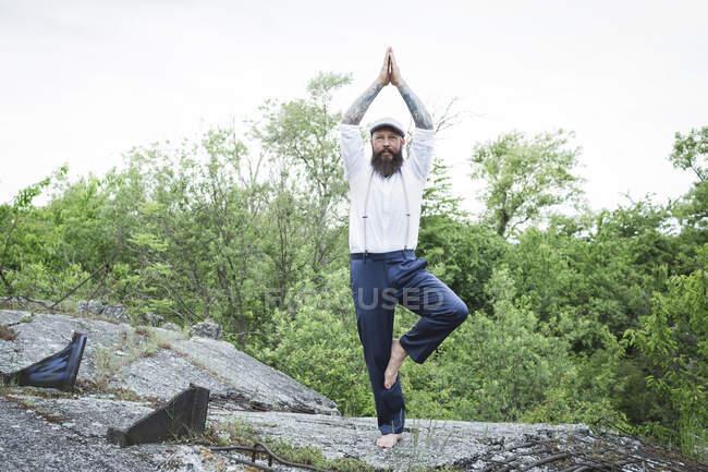 Бородатый мужчина в шапке практикует позу дерева на скале против деревьев — стоковое фото