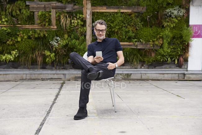 Зрелый мужчина с помощью смартфона, сидя на стуле во дворе — стоковое фото