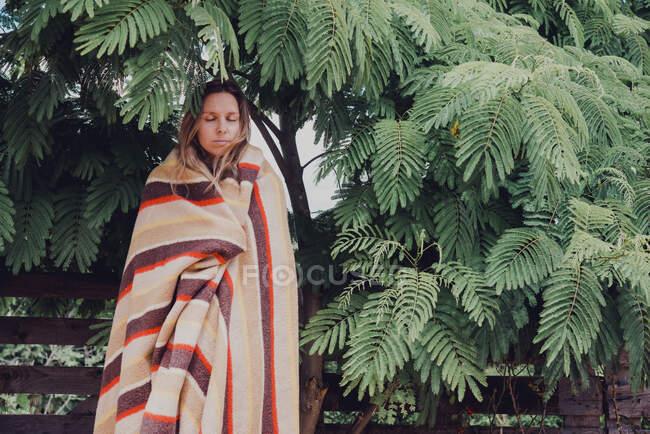 Mujer con los ojos cerrados envuelta en manta de pie junto al árbol de acacia dealbata en el parque - foto de stock