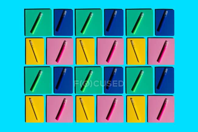Patrón de cuadernos coloridos y plumas de fieltro a juego - foto de stock