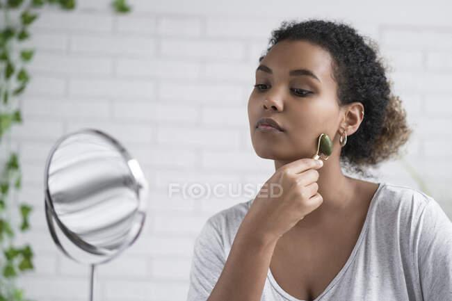 Primer plano de mujer joven masajeando la cara con rodillo de jade mientras se mira en el espejo en casa - foto de stock