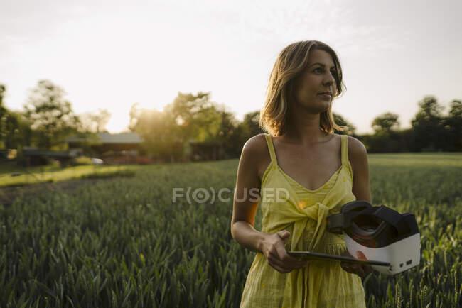 Jovem em um campo de grãos no campo segurando tablet e óculos VR — Fotografia de Stock