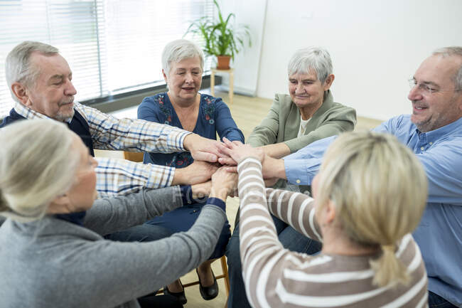 Група активних старшокласників складає руки, що символізує солідарність. — стокове фото