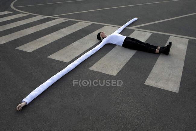 Woman with long artificial hands lying on crosswalk — Fotografia de Stock