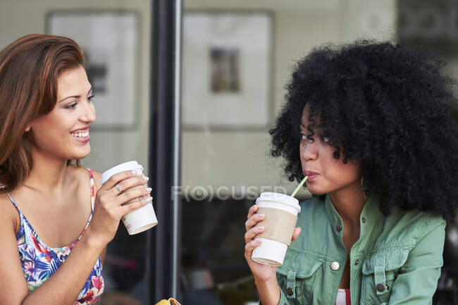 Girlfriends with coffee to go in cafe - foto de stock