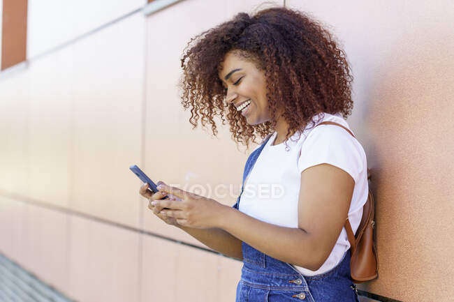 Happy young woman with afro hair using smart phone while standing by wall in city — Stock Photo