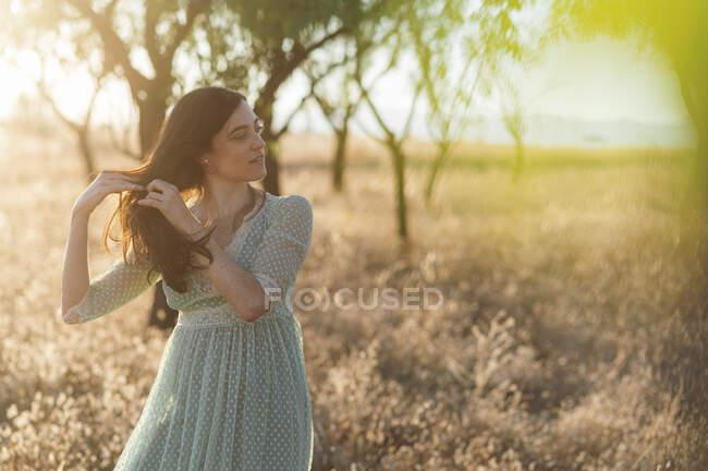 Giovane donna con le mani nei capelli in piedi in fattoria durante il tramonto — Foto stock