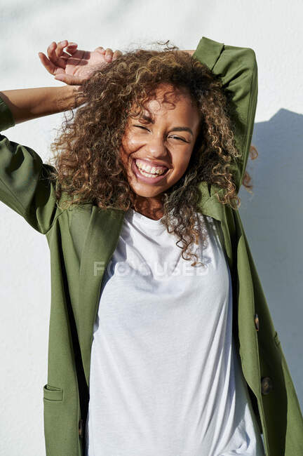 Mujer alegre de pie con las manos detrás de la cabeza durante el día soleado - foto de stock