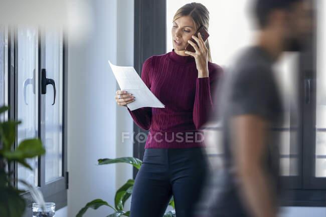 Empresária falando por telefone inteligente, enquanto colega de trabalho do sexo masculino andando no escritório — Fotografia de Stock
