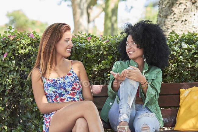 Copines parler et assis sur le banc — Photo de stock