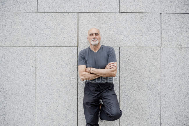Confident senior man with arms crossed standing against wall in city - foto de stock