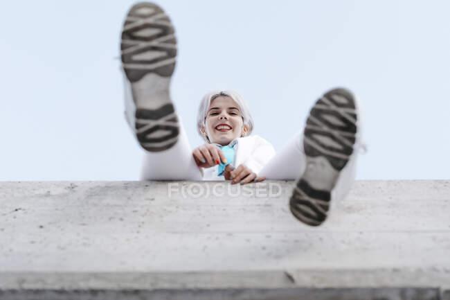 Sorrindo jovem mulher sentada na parede de retenção contra o céu limpo na cidade — Fotografia de Stock