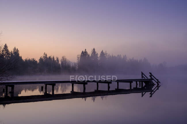 Jetty en la orilla del lago Kirchsee al amanecer brumoso - foto de stock