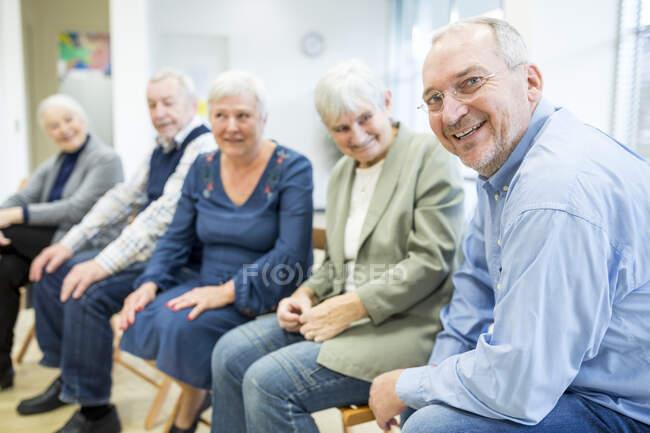 Пенсионеры, участвующие в групповом мероприятии в доме престарелых — стоковое фото