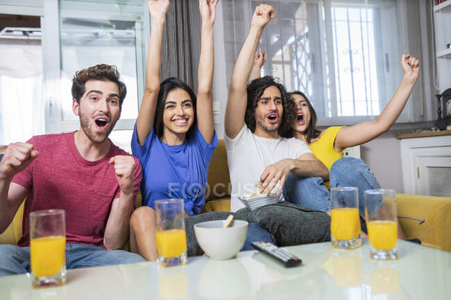 Cheerful young male and female fans cheering while watching TV at home — стоковое фото