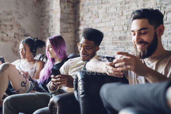 Група друзів сидить на дивані в горищі за допомогою смартфонів. — Stock Photo