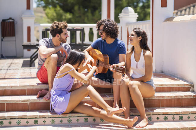 Happy young multi-ethnic friends enjoying while sitting with guitar on steps at terrace during sunny day — Stock Photo