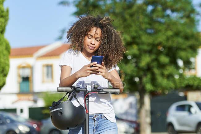Mujer usando un teléfono inteligente mientras está de pie con scooter eléctrico durante el día soleado - foto de stock
