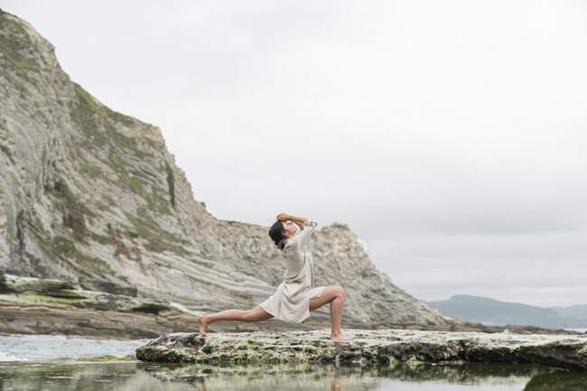 Молодая женщина танцует на скале на пляже против неба — стоковое фото