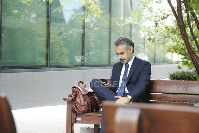 Businessman using phone while sitting on bench — стоковое фото