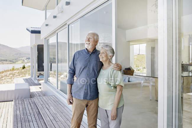 Счастливая пожилая пара, стоящая в роскошном пляжном доме — стоковое фото