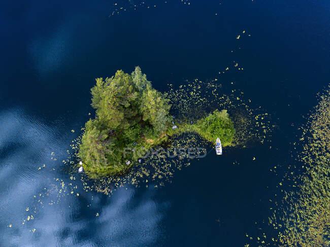 Vista aérea del barco a la izquierda en la orilla de un pequeño islote verde en el río Vuoksi - foto de stock