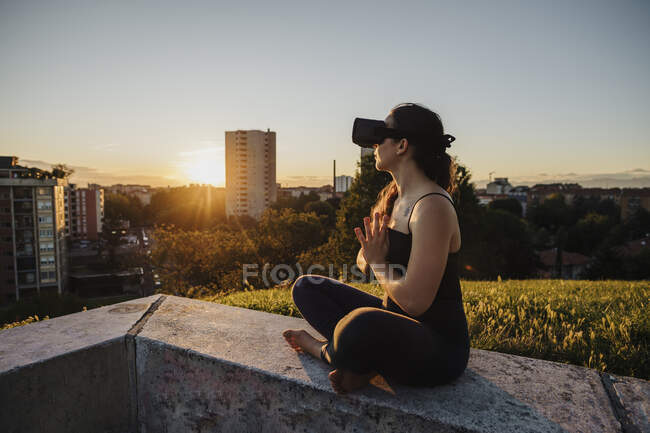 Relaxed woman using VR glasses while performing yoga in prayer positon on retaining wall in city — стокове фото