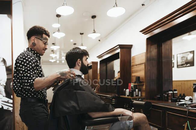 Peluquería de moda peinado cabello de hombre en el salón - foto de stock