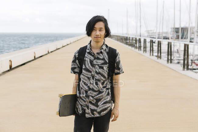 Молодой человек держит скейтборд, стоя на набережной в городе — стоковое фото
