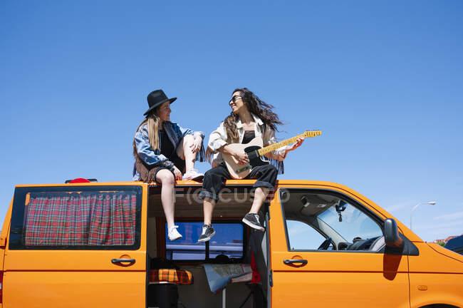 Dos mujeres sentadas en el techo de la camioneta, tocando la guitarra - foto de stock