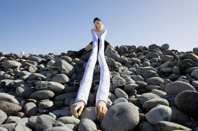 Thoughtful woman with artificial long hands sitting on pebbles against clear sky — Fotografia de Stock