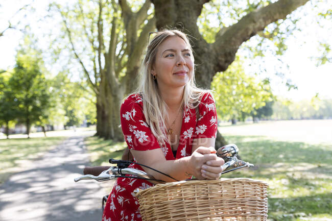 Thoughtful woman leaning on bicycle at public park — Stock Photo