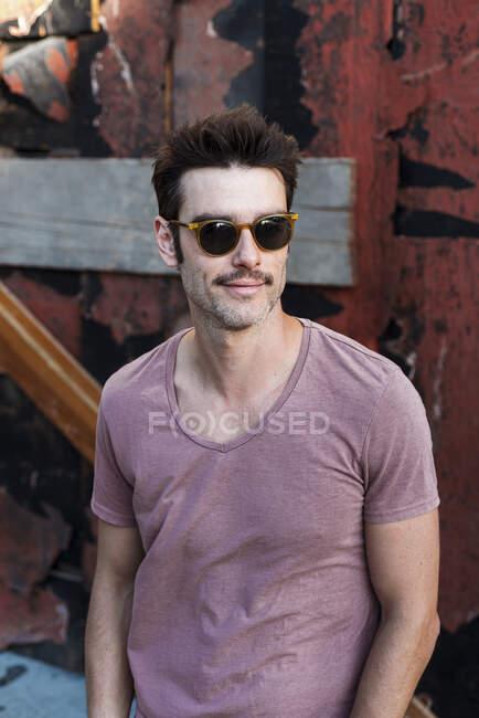 Hombre adulto medio usando gafas de sol de pie contra la vieja pared en la ciudad - foto de stock