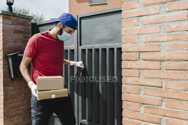 Мужчина почтальон, стоящий у ворот дома и доставляющий посылку во время пандемии — стоковое фото