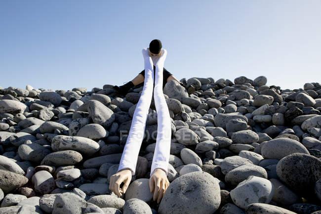 Жінка зі штучними довгими руками сидить на камінцях проти ясного неба. — стокове фото