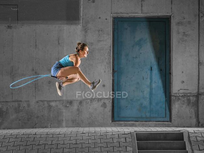Молодая женщина прыгает через скакалку к бетонной стене под мостом — стоковое фото