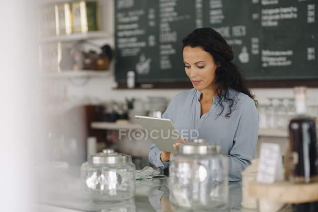 Доросла жінка за допомогою цифрового планшета стоїть за прилавком у кав