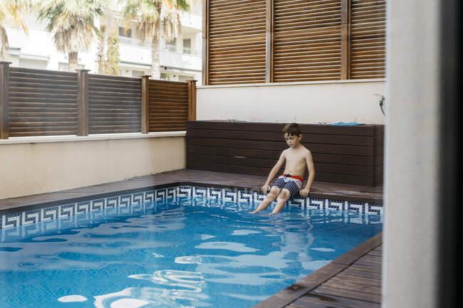 Boy sitting at pool edge during summer — Stock Photo