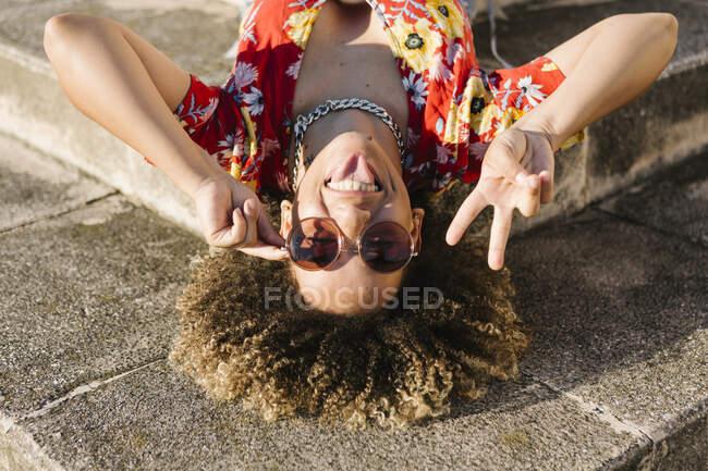 Mujer joven de moda sobresaliendo de la lengua mientras muestra signo de paz en los pasos - foto de stock