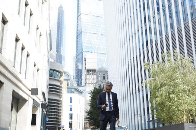 Businessman texting through mobile phone in city — стокове фото