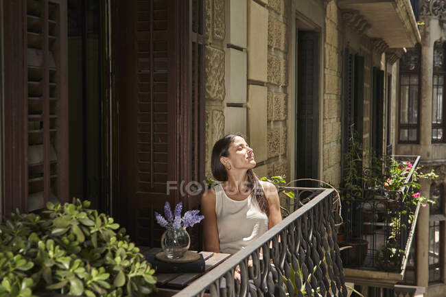 Woman with closed eyes relaxing in balcony — Stock Photo