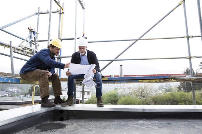 Архітектор і будівельник обговорюють план, сидячи на риштуванні проти ясного неба. — стокове фото