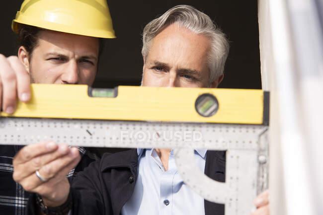 Gros plan de l'architecte et du travailleur de la construction mesurant le cadre de fenêtre vu à l'extérieur — Photo de stock