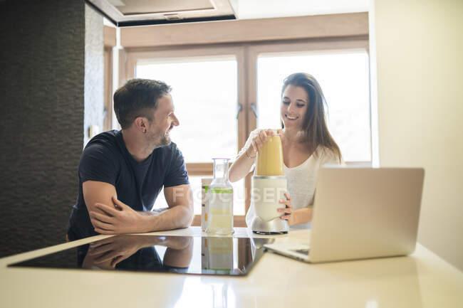 Sonriente hombre hablando con la mujer usando licuadora en la isla de la cocina en casa - foto de stock