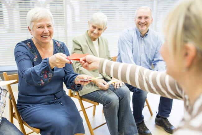 Старші на пенсії ходять на групову терапію, використовуючи барвисті паперові картки. — стокове фото