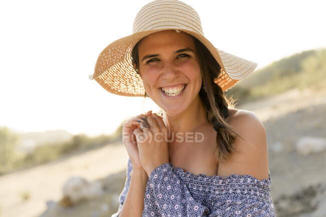 Glückliche junge Frau mit Sonnenhut an sonnigem Tag — Stockfoto