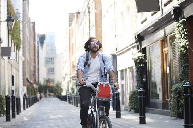 Portrait of young man riding on rental bike in the city, London, UK — Foto stock